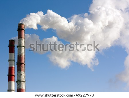 Two smoking towers against the pure blue sky. - stock photo