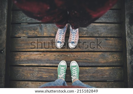 two sneakers behind each others on the wooden background as a sign of love - stock photo