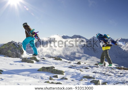 Two snowboarder climbing up the mountain - stock photo