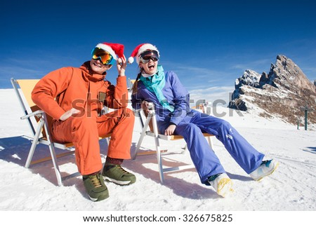 two snowboarders on top of the mountain having fun sitting on chair chaise lounge in santa hats