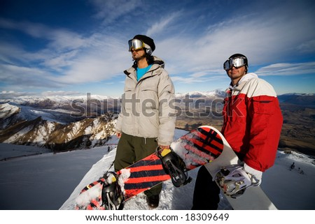 Two snowboarders stand on a peak over looking a spectacular view - stock photo