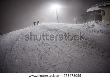 Two Snowboarders Strap in to their boards at the top of a chilly mountain at night. It looks like a frigid frosty scene at this ski area - stock photo