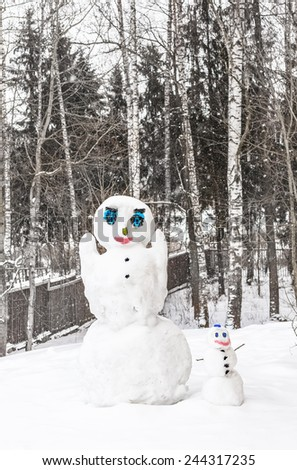 two snowmen against trees - stock photo