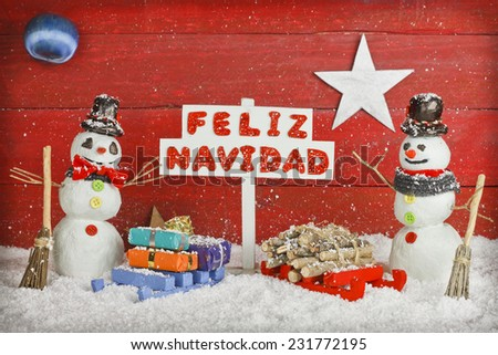 Two snowmen holding a sign with the words Merry Christmas written on spanish - stock photo