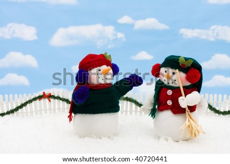 Two snowmen on a white picket fence with garland on a  sky background, gingerbread house