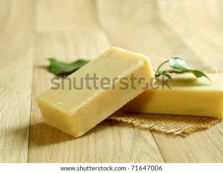 two soap and green leaf on wooden - stock photo