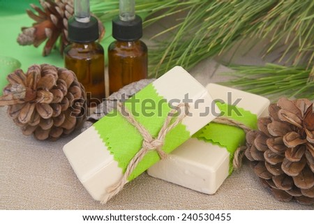 Two soap bars with pine tree essential oil.Pine tree essential oil in the background