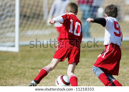 two soccer boys fighting for the ball with goalie in the background - stock photo