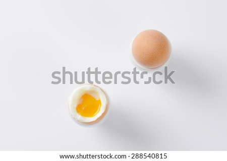 two soft boiled eggs in egg cups on white background - stock photo