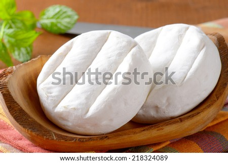two soft cheeses with white mold on wooden bowl - stock photo