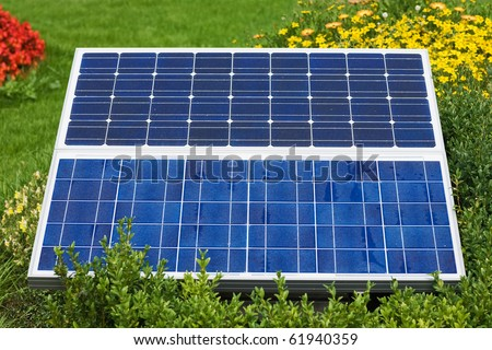 Two solar panels in meadow with flowers - stock photo