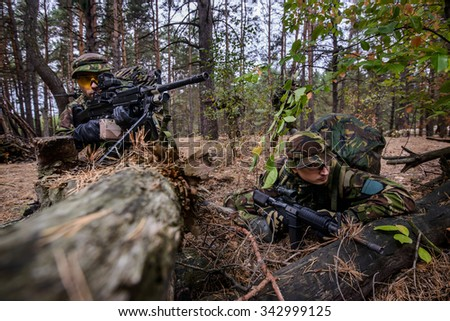 Two soldiers hiding in the woods waiting for attack