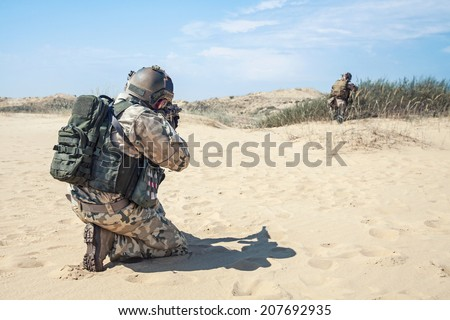 Two soldiers in the desert during the military operation - stock photo