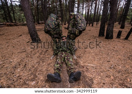 Two soldiers pull unconscious soldier from the battlefield in forest - stock photo