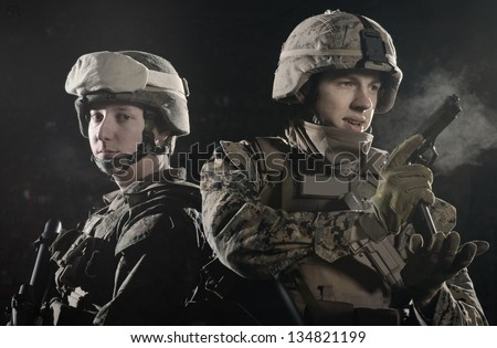 Two soldiers shoulder to shoulder, keeping defenses - stock photo