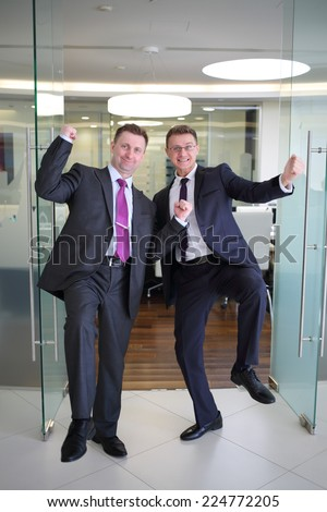 Two solid businessmen triumph at the entrance to the conference hall - stock photo