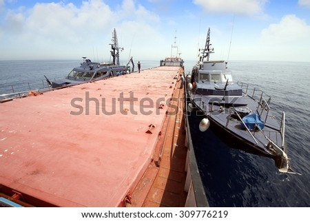 Two spanish coastguards controling a general cargo vessel - stock photo