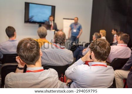 two speakers and the audience rear view at the business conference - stock photo