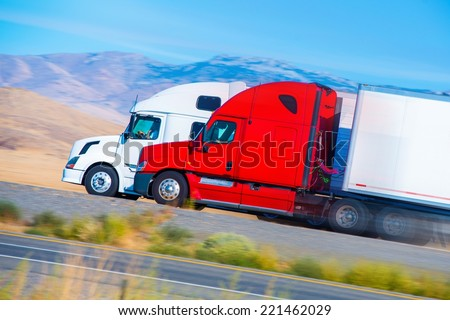 Two Speeding Semi Trucks on the Nevada Highway, USA. Trucking in America.  - stock photo