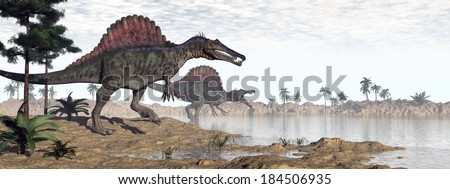 Two spinosaurus dinosaurs walking to the water in desert landscape by morning light - stock photo