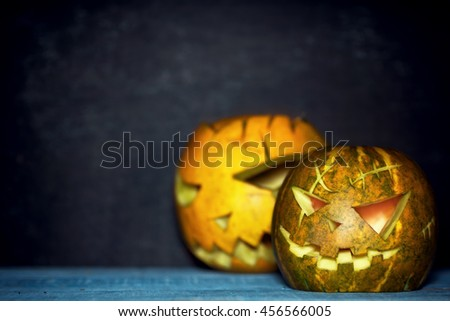 Two spooky pumpkin lanterns in darkness. Blue ang orange. Rustic halloween background. Text space - stock photo