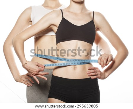 two sport girls measuring themselves isolated on white, inflated press - stock photo