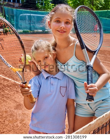Two sport kids girl with racket and ball on  brown tennis court. - stock photo