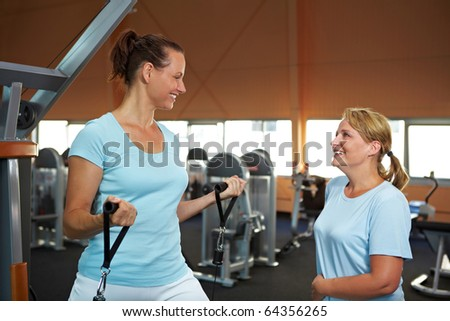 Two sportive women in gym talking to each other - stock photo