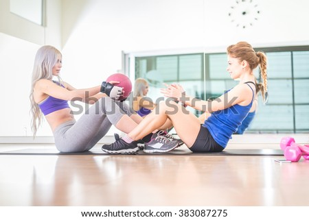 Two sportive women training abs with weighted ball in a gym - Girls working out to shape their body - stock photo