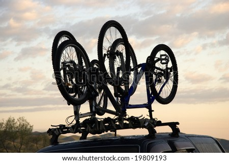 Two sports bicycles over jeep at sunrise in trip - stock photo