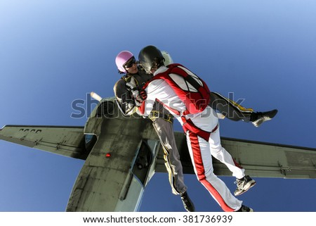 Two sports parachutist jumping out of an airplane. - stock photo