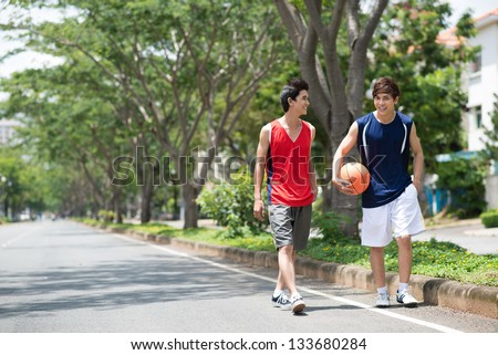 Two sportsmen walking in the park with a ball