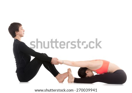 Two sporty people practicing yoga, girl is stretching in seated forward bend pose, paschimottanasana with assistance of her partner or coach - stock photo