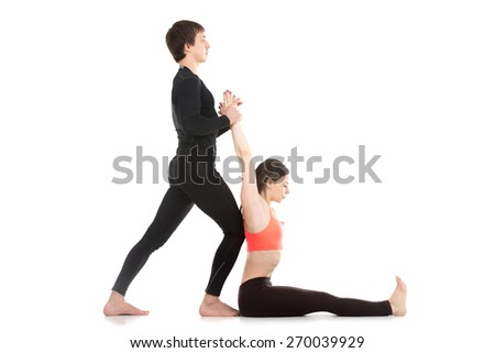Two sporty people practicing yoga, young man assisting girl doing seated forward bend pose, paschimottanasana, side view - stock photo