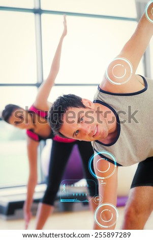 Two sporty people stretching hands at yoga class against fitness interface