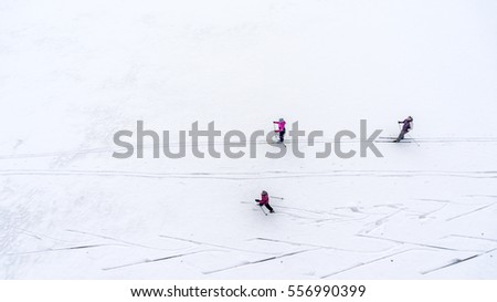 Two sporty woman and one child skiing on the snowy icy lake. Aerial view