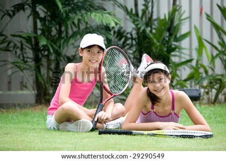 Two sporty young girls in tennis outfit with rackets, outdoor