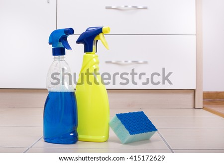 Two spray bottles with scrubber sponge on the tiled floor in the kitchen - stock photo