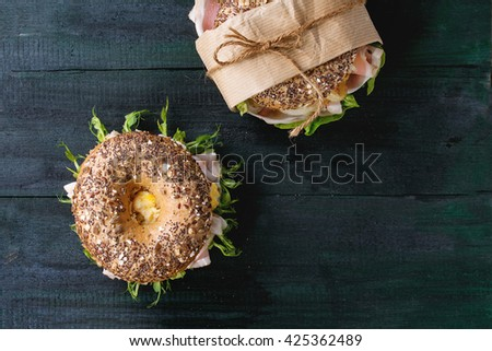 Two sprinkle seeds Whole Grain bagels with fried onion, scrambled eggs, green salad and prosciutto ham over dark wooden textured background. Top view. With copy space - stock photo