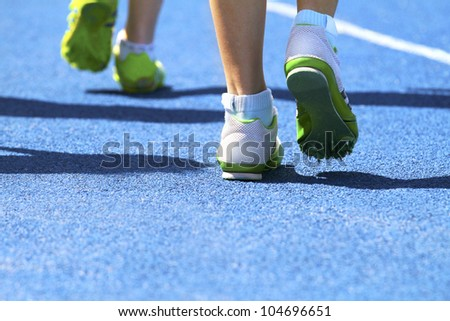 Two sprinters warming up for race competition - stock photo