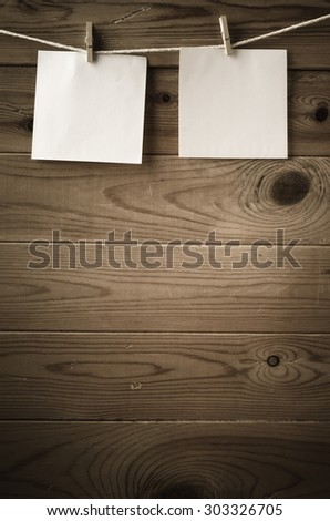 Two squares of blank paper, pegged to a string clothes line, with wood plank fence in the background.  Low saturation and vignette gives a retro or vintage feel. - stock photo
