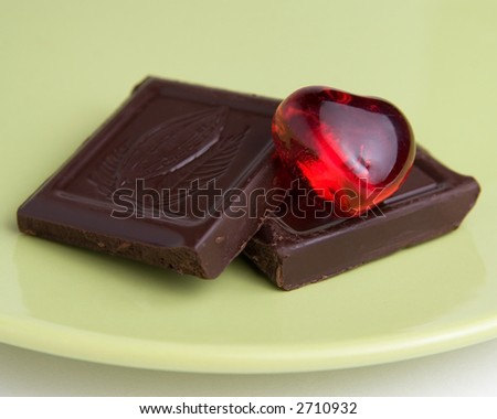 Two squares of rich dark chocolate with a red heart on a green plate.  Love and chocolate. - stock photo