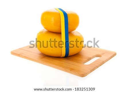 Two stacked whole Swedish cheeses isolated over white background
