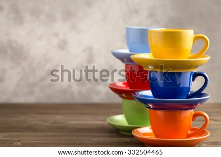 Two stacks multicolored cups on table from right side of gray background - stock photo