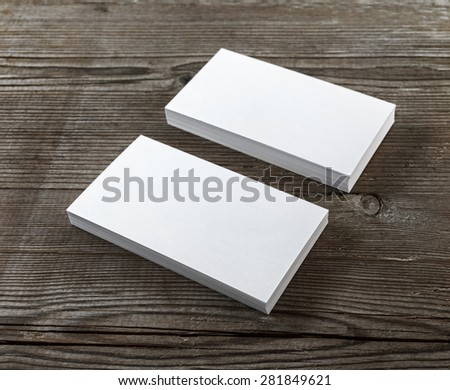 Two stacks of blank business cards on a dark wooden background. Template for branding identity. Shallow depth of field. Selective focus. - stock photo