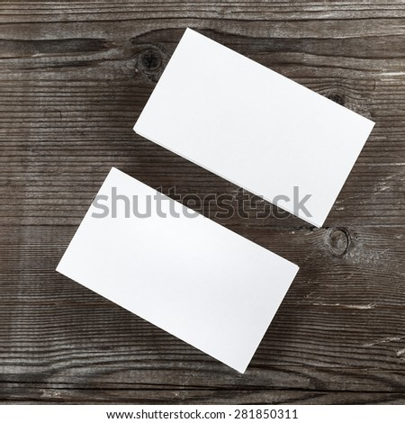 Two stacks of blank business cards on a dark wooden background. Template for branding identity. Top view. - stock photo