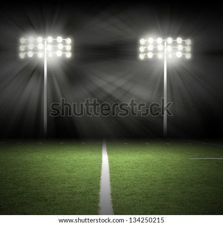 Two Stadium football game lights are shinning on a green grass field for a sport concept. - stock photo