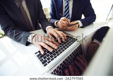 Two staff members working with laptop and notebook. - stock photo