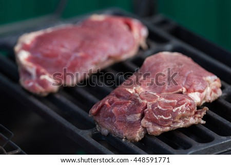 Two stakes are fried on the heated grill lattice - stock photo