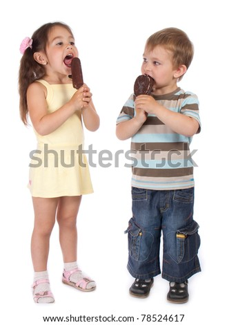 Two standing little children eating chocolate ice cream - stock photo